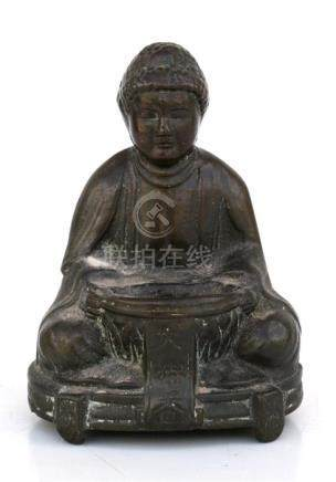 A Chinese bronze incense burner in the form of a seated Buddha, 10cms (4ins) high.