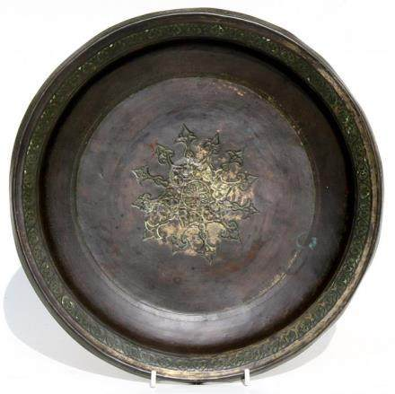 An Islamic bronze bowl with central star motif within a foliate border, the remains of gilding,