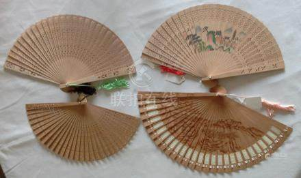 A collection of four Mid-20th Century sandalwood brise hand fans.