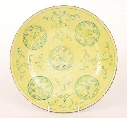 A 19th Century Chinese plate of circular dish form decorated with green mon roundels over a yellow