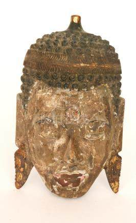 A carved wooden face mask of a Buddha, possibly depicting Maitreya,