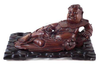 Chinese hardwood reclining Buddha, with pierced sit in wood stand, late 19th early 20th century, the