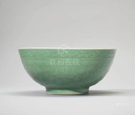 A LARGE CELADON-GLAZED CARVED AND MOULDED 'PEONY SCROLL' BOWL