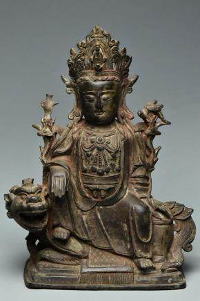 A MING BRONZE FIGURE OF GUANYIN SEATED ON A LION
