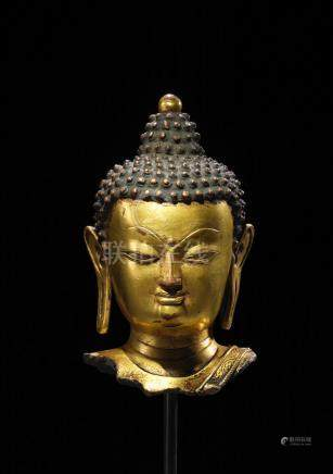 A GILT COPPER ALLOY HEAD OF BUDDHA  TIBET, 15TH CENTURY