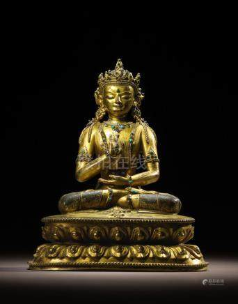 A GILT COPPER ALLOY FIGURE OF AMOGHASIDDHI TIBET, CIRCA 15TH CENTURY