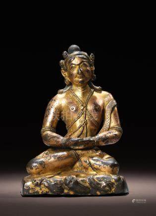 A GILT COPPER ALLOY FIGURE OF A MAHASIDDHA (POSSIBLY NAROPA) TIBET, CIRCA 17TH CENTURY