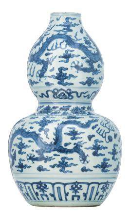 A Chinese blue and white double gourd vase, decorated with dragons and flaming pearls amid clouds, H 49,5 cm