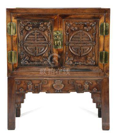 A Chinese hardwood cabinet on stand, of panelled construction, with a pair of cupboard doors