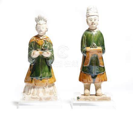 Two Chinese glazed pottery figures of attendants, wearing tunics, boots and hats and holding