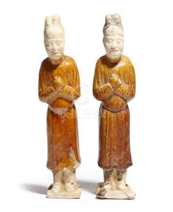 Two Chinese ochre glazed pottery figures, each wearing robes and sporting a headdress, Tang Dynasty,