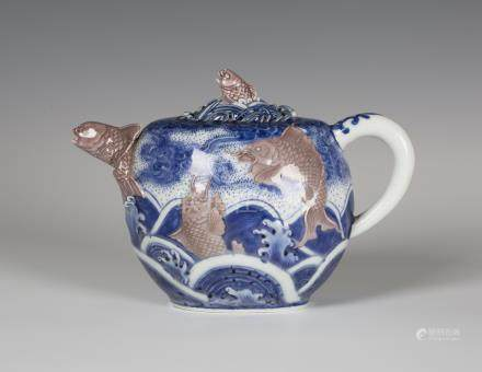 A Japanese underglaze blue and red porcelain teapot and cover by Makuzu Kozan, Meiji period, of oval