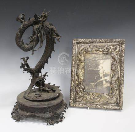 A Japanese metal figure of a coiling dragon on a crashing wave moulded circular base, height 41cm (