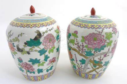 A pair of Famille Rose lidded vases / ginger jars of ovoid form,