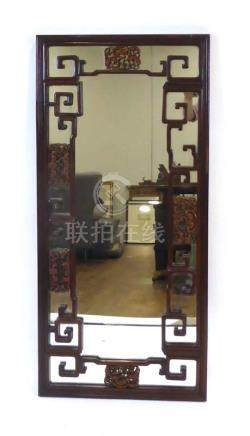 A late 19th/early 20th century Chinese hardwood wall mirror of rectangular form, typically carved,