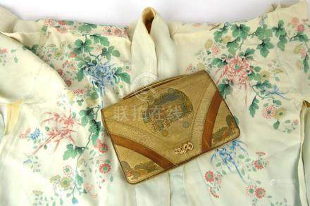 An early 20th century Japanese silk kimono decorated with sprays of blossoming chrysanthemum on a