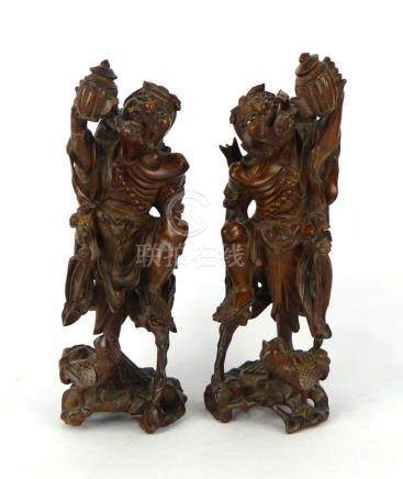 A pair of Chinese hardwood figures each modelled as a gentleman taking tea from a teapot,