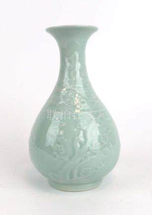 A Chinese celadon vase of squat ovoid form shallow relief decorated with cherry blossom,
