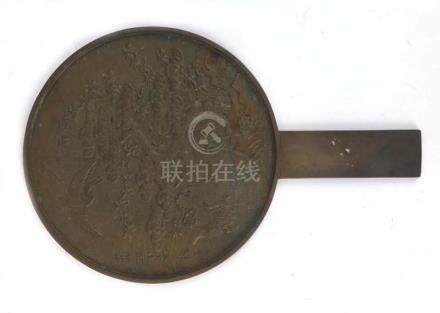 A Japanese brown patinated bronze hand mirror relief decorated with cranes and a tortoise beneath a