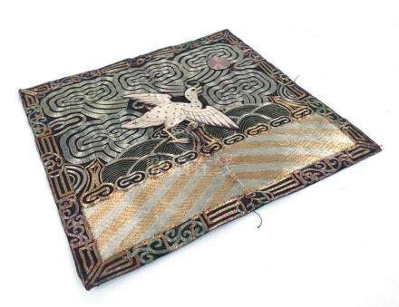 An early 20th century silk panel worked in gold and silvered coloured threads and depicting a bird