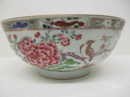 A late 18th century Chinese porcelain famille rose bowl decorated with peonies, trees, birds insects