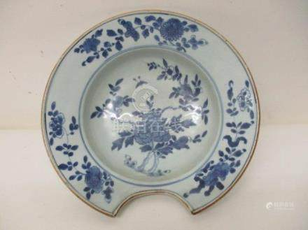 A mid 18th century Chinese blue and white shaving bowl decorated with a flowering tree, flowers