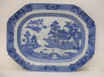 A late 18th century Chinese blue and white meat plate decorated with a lake, buildings, a bridge,