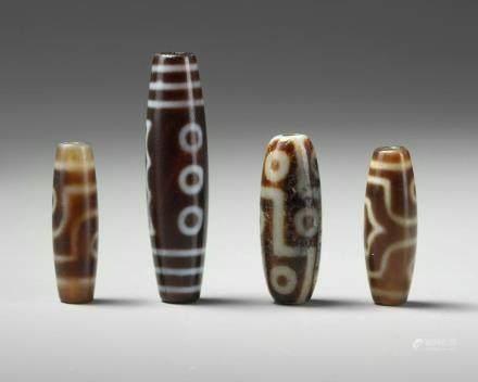 A group of four Tibetan dzi beads