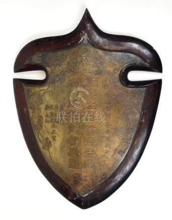 Escudo chino en bronce niquelado con inscripciones y flores.