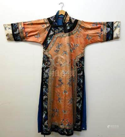 Deux Robes chinoises. L'une à fond saumon à motifs brodés de papillons, de branches de ceris