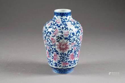 Vase sur Piédouche. A ornementation de rinceaux de fleurs à l'émail rose et en camaïeu de bl