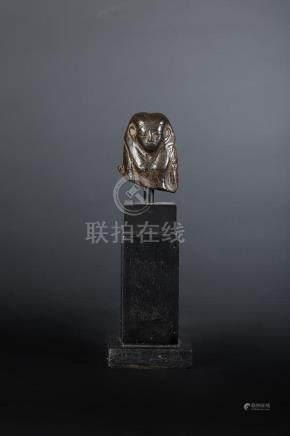 Fragment de statuette représentant un buste féminin. Elle porte une longue perruque triparti