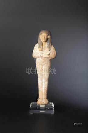 Oushebti portant la longue perruque tripartite peinte en noir et les bras croisés au niveau