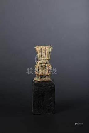 Amulette janiforme représentant le dieu Bès grimaçant coiffé de hautes plumes.Faïence verdât