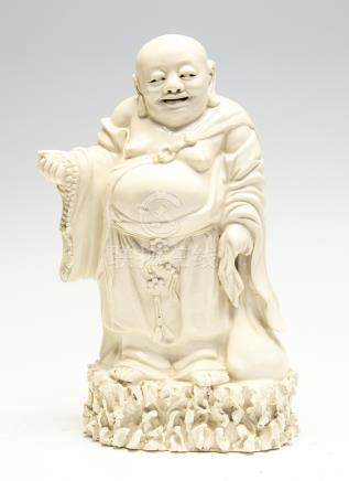 A Chinese blanc de chine figure of Budai, mid 20th Century, standing on a rocky outcrop,