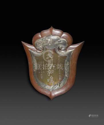 CHINE - Vers 1900Ecusson en bois sculpté fixé d'une plaque en argent? à décor ciselé d'une o