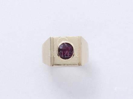 Bague chevalière en or 750 millièmes ornée d'un rubis ovale facetté en serti clos. Travail f