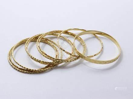 Ensemble en or 750 millièmes composé de 9 bracelets jonc stylisés.  Poids brut: 105.30 g l'e