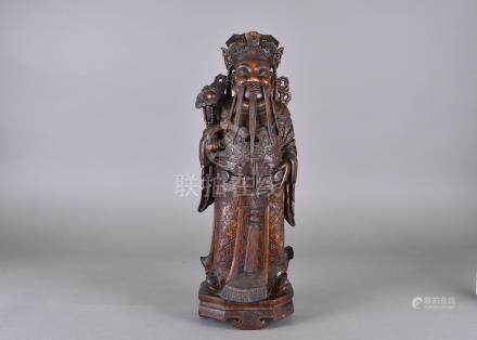 A late 19th Century Chinese hardwood carved model of an Emperor, wearing ornate robes and holding