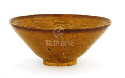 A Chinese tea bowl, Liao dynasty (907-1125), with a moulded motif of scrolling lotus and leaves ...