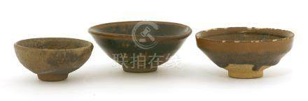 Three Chinese Jian ware tea bowls, Song Dynasty (960-1279), of conical form, the glaze falling ...