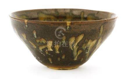 A Chinese tea bowl, in the style of Jizhou ware, the glaze of opaque and brown running to the foot ...