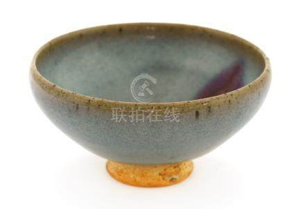 A Chinese Jun ware tea bowl, possibly Yuan dynasty (1279-1368), of tapering form with an inverted ...