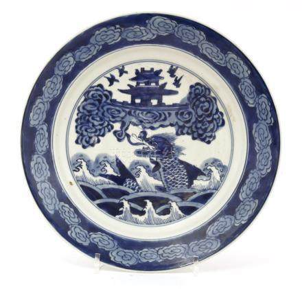 A Chinese blue and white dish, Kangxi (1662-1722), painted with a carp turning into a dragon ...
