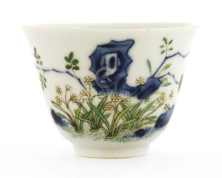 A Chinese wucai wine cup, Kangxi (1662-1722), painted with flowering narcissus by rocks, six ...