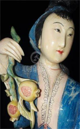 A carved and painted ivory okimono, early 20th century, of a lady holding a fruiting branch, on a
