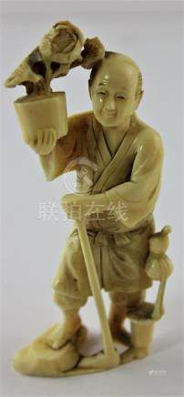 A Japanese Meiji period carved ivory okimono, of a man with walking stick carrying a pot of flowers,