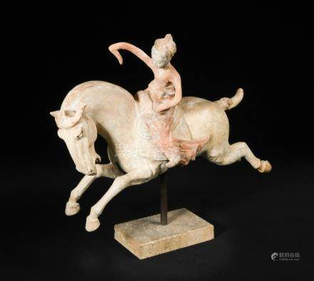 A red painted Tang dynasty pottery female polo player, astride a galloping horse, the horse