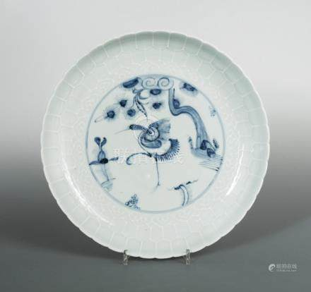 A Ming pale celadon dish, a crane to the centre in underglazed blue standing below a pine branch