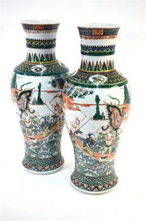 A pair of Chinese famille verte vases; each one with trumpet neck, and decorated with narrative